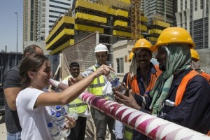 Dana El-Kalache and Ammar Al Alwan distribute water to workers on a construction site as part of the Sameness Project's campaign during the hot summer months. Antonie Robertson / The National